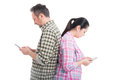 Couple standing back to back and texting
