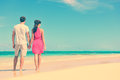Couple standing on beach travel holding hands rear view of multiethnic romantic shore young partners are watching sea Stock Photo