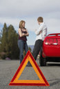Couple standing by breakdown car with warning triangle in foreground young red Stock Image