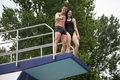 Couple standing on diving board at swimming pool platform public showing thumbs up Royalty Free Stock Images