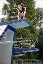 Couple standing on diving board at swimming pool platform public showing thumbs up Stock Image
