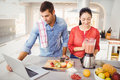 Couple standing with fruit juice while man using laptop Royalty Free Stock Photo