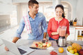 Couple standing with fruit juice while using laptop Royalty Free Stock Photo