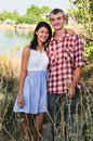 Couple standing in the grass near the lake portrait of young a Royalty Free Stock Image