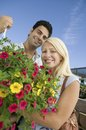Couple standing in plant nursery holding hanging plant portrait low angle view Royalty Free Stock Photo