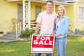 Couple Standing By For Sale Sign Outside Home Royalty Free Stock Photography