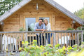Couple standing on terrace of wooden cabin