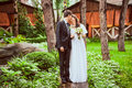 Couple standing together in forest against wooden toned photo of newly married houses Royalty Free Stock Photos
