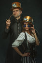 The couple steampunk. A man with a pipe and a girl with glasses Royalty Free Stock Photo