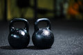 A couple of steel black kettlebells on a blurred background. A kettlebell on a gym floor. Workout. Copy space. Royalty Free Stock Photo