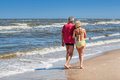 Couple strolling at coastline mature together sandy Stock Image