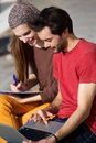 Couple students working on laptop together outdoors portrait of a Royalty Free Stock Photo