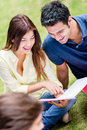 Couple studying outdoors of college students looking happy Royalty Free Stock Photo