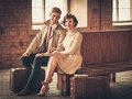 Couple with suitcases on a train station vintage style young Stock Image