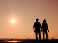 Couple on the sun man and women holding hands and watching Stock Photography