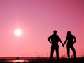Couple on the sun silhouette of a men and women who are holding hands Royalty Free Stock Images