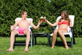 Couple sunbathing in back yard and toasting a young a with tropical drinks Stock Photos