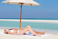 Couple sunbathing beautiful beach holiday under parasol Stock Photo