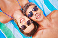 Couple sunbathing portrait of a young attractive and wearing sunglasses Stock Photo