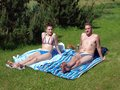 Couple sunbathing young men and women together on countryside Stock Photos