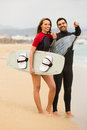 Couple with surf boards on the beach cheerful smiling young resting Stock Photos