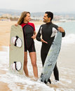 Couple with surf boards on the beach happy young Royalty Free Stock Images