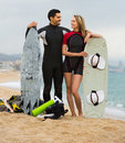Couple with surf boards on the beach young active cheerful resting Stock Image