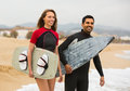 Couple with surf boards on the beach young cheerful resting Royalty Free Stock Photography