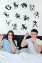 Couple surrounded showing up at horoscope zodiac signs man and surprised women in bedroom young in bed domestic atmosphere Royalty Free Stock Image