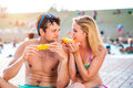 Couple in swimming suits at the pool eating corn Royalty Free Stock Photo