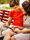 Couple with tablet pc sit on bench outdoor Royalty Free Stock Photography