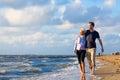 Couple take a walk at german north sea beach romantic through sand and waves Royalty Free Stock Photos
