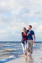 Couple take a walk at german north sea beach romantic through sand and waves Stock Photo