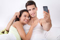 Couple taking a picture with mobile phone cheerful young in bed Stock Photo