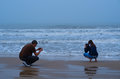Couple taking pictures of the surf in matagorda texas Royalty Free Stock Photos