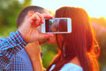 Couple taking self portrait photos with mobile smart phone Royalty Free Stock Photography