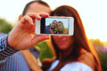 Couple taking self portrait photos with mobile smart phone Stock Photos