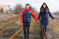 Couple taking a stroll along the railway tracks quiet lines holding hands as young women balances on metal track Royalty Free Stock Photography