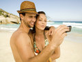 Couple taking their picture on the beach sandy Royalty Free Stock Photography