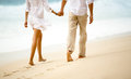 Couple taking a walk holding hands on the beach Royalty Free Stock Photo