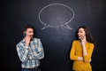 Couple talking on cell phone over chalkboard with speech bubble Royalty Free Stock Photo