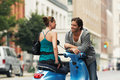 Couple talking by moped on street woman to men in Royalty Free Stock Photo