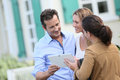 Couple talking to a real estate agent meeting outside new property Royalty Free Stock Photo