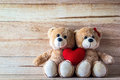 Couple teddy bear with pink heart shaped pillow on plank wood board valentine concept Royalty Free Stock Photos