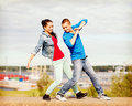 Couple of teenagers dancing outside summer holidays teenage and concept Stock Photography