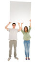 Couple of teenagers with white panel on background Royalty Free Stock Photography