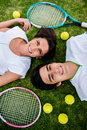 Couple of tennis players lying in the floor with rackets and balls Stock Photo