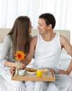 Couple with their breakfast on the bed Stock Images