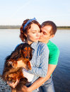 Couple with their dog on riverside during sunset Royalty Free Stock Images