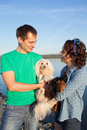 Couple with their dogs on riverside during sunset Royalty Free Stock Photos